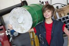Portrait d'un bidon à pétrole de transport de jeune mécanicien féminin heureux sur l'épaule dans l'atelier de voiture images libres de droits