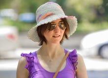 Portrait d'un chapeau de port et des lunettes de soleil de jeune femme de brune photo stock