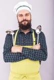 Portrait d'un chef barbu tenant deux grands ustensiles de cuisine, jeune homme image libre de droits