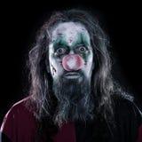Portrait d'un clown rampant devant le fond noir, concept photos stock