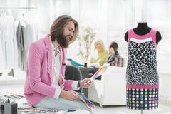 Portrait d'un concepteur d'habillement s'asseyant sur un bureau dans le studio photographie stock libre de droits