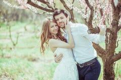 Portrait d'un couple de sourire heureux : jeune homme beau tenant la belle jeune femme dehors un jour ensoleillé lumineux de photo libre de droits