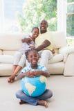 Portrait d'un couple de sourire heureux se reposant sur le divan et la fille prenant un globe image libre de droits