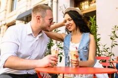 Portrait d'un couple de sourire mangeant la crème glacée et ayant l'amusement Photos libres de droits