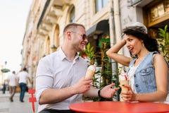Portrait d'un couple de sourire mangeant la crème glacée et ayant l'amusement Images stock