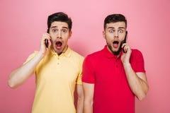 Portrait d'un couple gai étonné parlant aux téléphones portables Images libres de droits