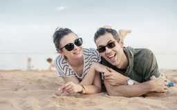 Portrait d'un couple gai et décontracté s'étendant sur le sable Images stock