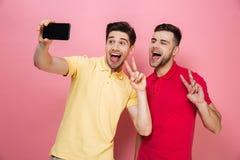 Portrait d'un couple gai heureux prenant un selfie Photo stock