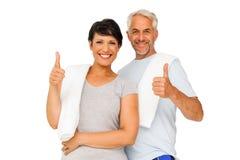 Portrait d'un couple heureux d'ajustement faisant des gestes des pouces  Images stock