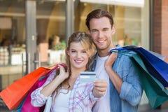 Portrait d'un couple heureux montrant leur nouvelle carte de crédit Images libres de droits