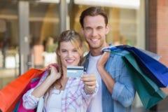 Portrait d'un couple heureux montrant leur nouvelle carte de crédit Photo stock