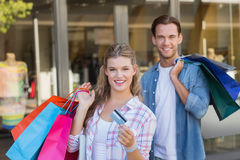 Portrait d'un couple heureux montrant leur nouvelle carte de crédit Photos stock