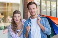 Portrait d'un couple heureux montrant leur nouvelle carte de crédit Photos libres de droits