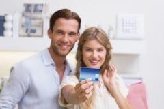 Portrait d'un couple heureux montrant leur nouvelle carte de crédit image libre de droits