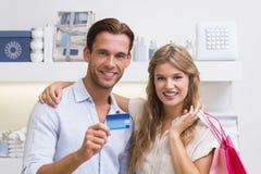Portrait d'un couple heureux montrant leur nouvelle carte de crédit image stock