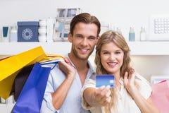 Portrait d'un couple heureux montrant leur nouvelle carte de crédit Images stock
