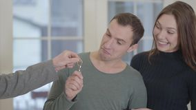 Portrait d'un couple heureux recevant les clés d'un vrai agent immobilier non reconnu et embrassant joyeux satisfait banque de vidéos