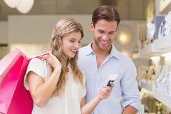 Portrait d'un couple heureux regardant le produit de beauté Images stock