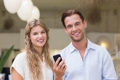 Portrait d'un couple heureux regardant le smartphone Images libres de droits