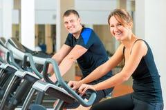 Portrait d'un couple heureux sur un vélo stationnaire Images libres de droits