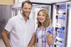 Portrait d'un couple occasionnel de sourire ayant une bouteille d'eau Photo stock