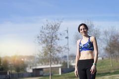 Portrait d'un coureur féminin souriant avant de pulser au parc images stock