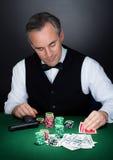 Portrait d'un croupier regardant jouant des cartes Photos libres de droits