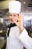 Portrait d'un cuisinier féminin de sourire faisant des gestes le signe correct Photos stock