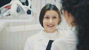 Portrait d'un dentiste et d'un assistant de sourire, regardant le presse-papiers dans une clinique dentaire moderne Habillé dans  banque de vidéos