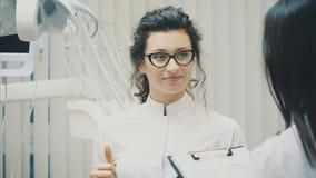 Portrait d'un dentiste et d'un assistant de sourire, regardant le presse-papiers dans une clinique dentaire moderne Habillé dans  clips vidéos