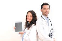 Portrait d'un docteur avec son infirmière montrant un comprimé Images libres de droits