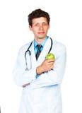 Portrait d'un docteur masculin de sourire tenant la pomme verte sur le blanc Image libre de droits