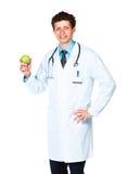 Portrait d'un docteur masculin de sourire tenant la pomme verte sur le blanc Photo libre de droits