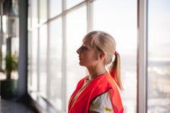 Portrait d'un employé féminin dans un gilet orange de robe longue dans l'espace de fonctionnement d'une salle de production Images libres de droits