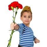Portrait d'un enfant dans l'uniforme militaire avec des fleurs dans des mains Est 9 mai Victory Day Photographie stock libre de droits