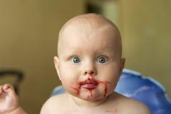 Portrait d'un enfant drôle enduit du jus de framboise photographie stock