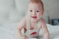 Portrait d'un enfant en bas âge de sourire sur le lit Images stock