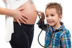 Portrait d'un enfant et d'une femme enceinte Écoute ce qui continue dans mon ventre du ` s de mère Image stock