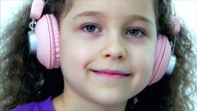 Portrait d'un enfant mignon avec les cheveux bouclés, petite fille caucasienne dans un T-shirt pourpre avec une écoute rose d'éco banque de vidéos