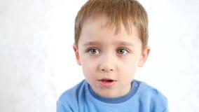 Portrait d'un enfant réfléchi, sur un fond blanc banque de vidéos