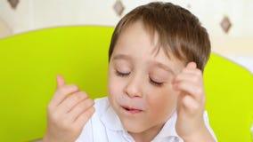 Portrait d'un enfant riant heureux Un petit garçon mange la sucrerie délicieuse banque de vidéos