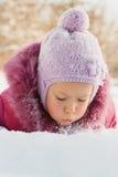 Portrait d'un enfant se trouvant sur la neige Photographie stock libre de droits