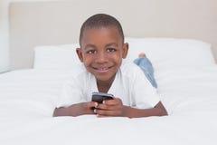 Portrait d'un garçon assez petit à l'aide du smartphone dans le lit images libres de droits