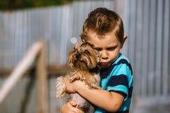 Portrait d'un garçon avec le chien de Yorkshire Terrier sur une promenade Amitié d'animal familier d'enfants Image libre de droits