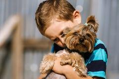 Portrait d'un garçon avec le chien de Yorkshire Terrier sur une promenade Amitié d'animal familier d'enfants Photos libres de droits
