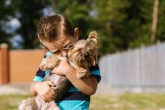 Portrait d'un garçon avec le chien de Yorkshire Terrier sur une promenade Amitié d'animal familier d'enfants Photos stock