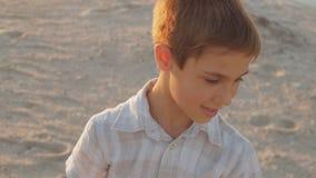 Portrait d'un garçon de 10 ans dans une chemise blanche sur une plage d'été au coucher du soleil clips vidéos