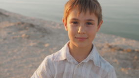 Portrait d'un garçon de 10 ans souriant sur une plage d'été en mer sur un fond au coucher du soleil clips vidéos