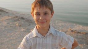 Portrait d'un garçon de 10 ans souriant sur une plage d'été en mer sur un fond au coucher du soleil banque de vidéos