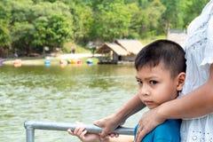 Portrait d'un garçon et le radeau en bois dans les réservoirs d'eau photographie stock